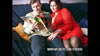 Одетая зрелая с коротенькой стрижкой преобладает над племянником на деревянном полу и на диване